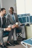 colegas do negócio que esperam o voo na entrada do aeroporto com café Fotografia de Stock Royalty Free
