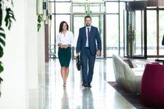 Colegas do negócio que interagem um com o otro ao andar no corredor no escritório imagem de stock royalty free