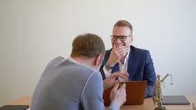 Colegas do negócio que riem do gracejo do divertimento no local de trabalho no escritório moderno filme