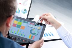 Colegas do negócio que trabalham e que analisam figuras financeiras em uma tabuleta digital Foto de Stock Royalty Free