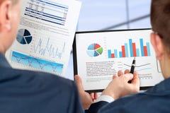 Colegas do negócio que trabalham junto e que analisam figuras financeiras no gráficos Fotografia de Stock Royalty Free