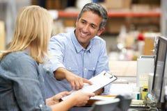 Colegas do negócio que trabalham na mesa no armazém Fotos de Stock Royalty Free