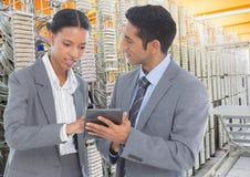 Colegas do negócio que usam a tabuleta digital contra sistemas do servidor de base de dados no fundo foto de stock royalty free