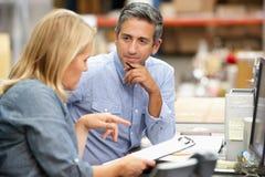 Colegas do negócio que trabalham na mesa no armazém Imagem de Stock Royalty Free