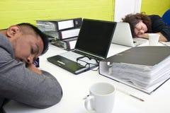 Colegas dormidos en su escritorio respectivo Foto de archivo