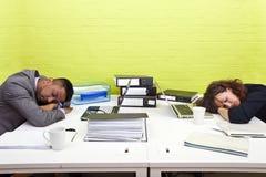 Colegas dormidos en su escritorio respectivo Imágenes de archivo libres de regalías