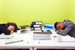 Colegas dormidos en su escritorio respectivo Imagen de archivo libre de regalías