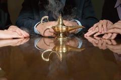 Colegas em torno de uma lâmpada de fumo dos gênios Imagens de Stock