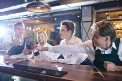 Colegas emocionados del restaurante que tintinean las botellas de cerveza en la cuenta de la barra imágenes de archivo libres de regalías
