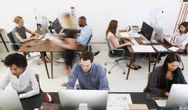 Colegas en los ordenadores en una oficina abierta del plan, vista delantera foto de archivo