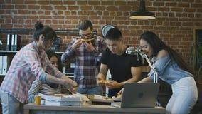 Colegas en oficina que comen la pizza junta almacen de metraje de vídeo