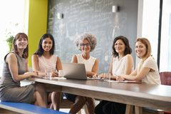 Colegas fêmeas do trabalho na reunião informal que olha à câmera imagens de stock royalty free