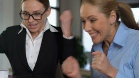 Colegas fêmeas felizes que leem o e-mail no portátil, negócio bem sucedido, realização video estoque