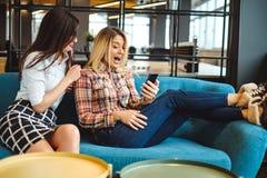 Colegas fêmeas na ruptura surpreendidos ao olhar o pho móvel imagens de stock royalty free