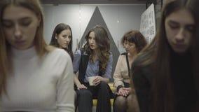 Colegas fêmeas que sentam-se junto em duas fileiras que têm a ruptura no trabalho Mulheres novas e maduras que conversam e que bi video estoque