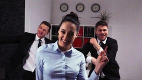 Colegas felizes que dançam na sala do escritório filme