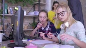Colegas femeninos jovenes que solucionan problemas y materias relacionadas del trabajo de la discusión en oficina almacen de video