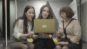 Colegas femeninos que se sientan junto teniendo rotura en el trabajo Mujeres jovenes y maduras que charlan detrás de las partes p metrajes