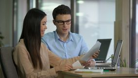 Colegas jovenes que comparan los gráficos, discutiendo el crecimiento de clientes, trabajo en equipo almacen de video