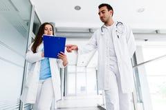 Colegas médicos novos que analisam o cartão ao andar através do hospital imagem de stock