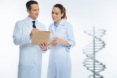 Colegas médicos que fazem anotações ao discutir a genética fotografia de stock royalty free