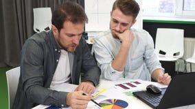 Colegas masculinos do negócio que fazem o documento junto no escritório foto de stock