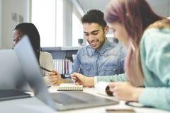 Colegas masculinos e fêmeas novos de sorriso que fazem trabalhos de casa junto Imagem de Stock Royalty Free