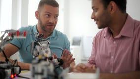 Colegas masculinos radiantees que discuten ventajas del legado robótico