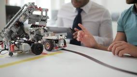 Colegas milenarios que usan la tableta digital mientras que prueba las máquinas robóticas