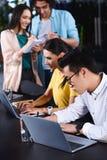 colegas multiétnicos del negocio que usan los ordenadores portátiles en la tabla mientras que sus colegas que escriben en libro d foto de archivo libre de regalías