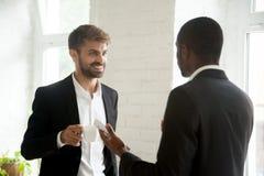 Colegas multiétnicos que tienen conversación del negocio durante coffe imagen de archivo