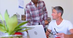 colegas Multi-étnicos del negocio que discuten sobre la tableta digital en la oficina moderna 4k metrajes