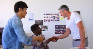 colegas Multi-étnicos do negócio que agitam as mãos no escritório moderno 4k vídeos de arquivo