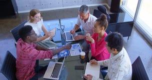 colegas Multi-étnicos do negócio que discutem sobre gráficos em uma reunião no escritório moderno 4k filme