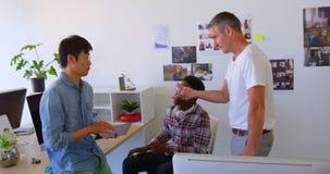 colegas Multi-étnicos do negócio que interagem um com o otro no escritório moderno 4k filme