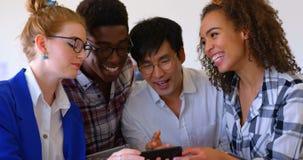 Colegas multi-étnicos felizes do negócio que usam o telefone celular no escritório moderno 4k vídeos de arquivo