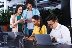 colegas multiculturales del negocio que usan los ordenadores portátiles en la tabla mientras que sus colegas que se colocan con l fotografía de archivo