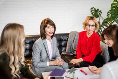 Colegas multirraciales de las mujeres que se sientan alrededor de la tabla y del gráfico de dibujo imagen de archivo libre de regalías