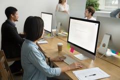 Colegas multirraciales que trabajan junto en los equipos de escritorio adentro imagenes de archivo