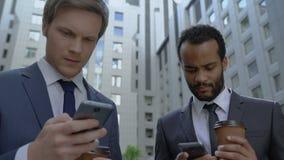 Colegas na ruptura de café, procurando a informação em dispositivos, usando o app móvel filme