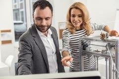 Colegas otimistas que ajustam parâmetros para a impressora 3D através do computador Foto de Stock