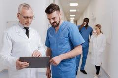 Colegas otimistas que usam o dispositivo moderno no hospital Fotografia de Stock
