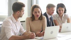 Colegas ou conversa do gerente e do cliente no portátil do uso do escritório filme