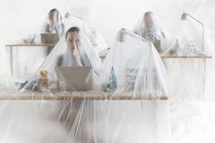Colegas prendidos do negócio que usam portáteis nas mesas cobertas no plástico imagens de stock