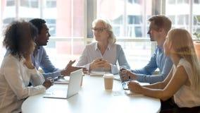 Colegas profissionais multiculturais da equipe que mandam a conversação sentar-se na tabela de conferência imagem de stock royalty free