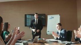 Colegas que aplauden al hombre de negocios en oficina metrajes