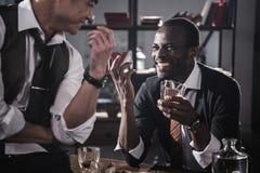 Colegas que beben el alcohol mientras que pasa el tiempo junto después de trabajo fotografía de archivo libre de regalías