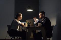 Colegas que discuten estrategias empresariales en oficina en la noche fotos de archivo