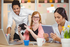 Colegas que guardam a câmera com a mulher de negócios que usa a tabuleta digital Fotos de Stock Royalty Free