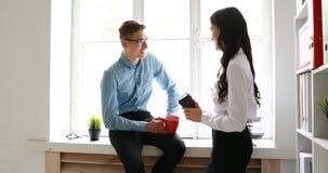 Colegas que hablan y que beben el café mientras que en la ventana en oficina